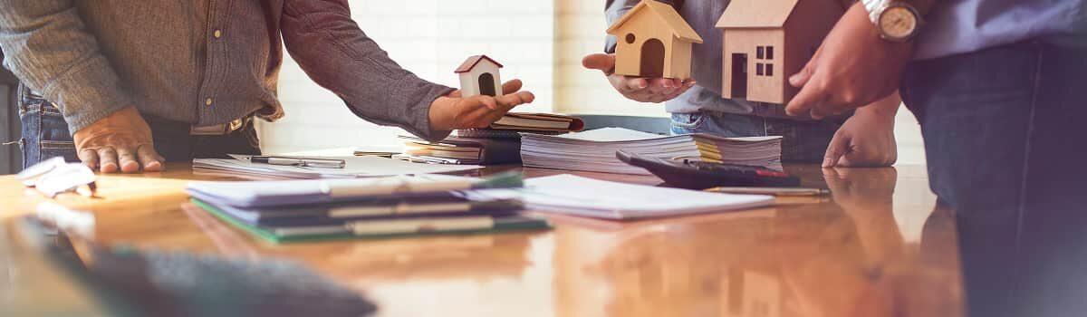 Investors holding small house models Bergan & Company Property Management Denver, Centennial, Colorado