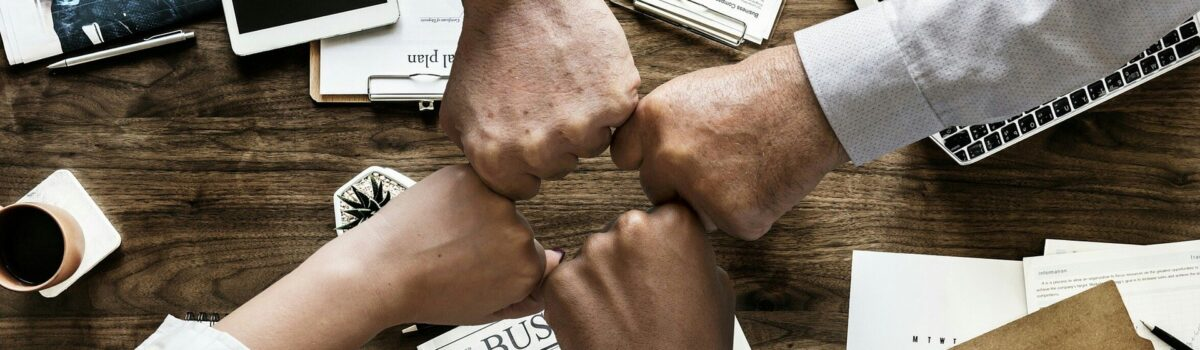four coworkers with knuckles all in Bergan & Company Property Management Denver, Centennial, Colorado