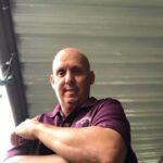 man wearing maroon shirt looking down at camera Bergan & Company Property Management Denver, Centennial, Colorado